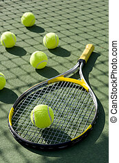 Tennis - A group of tennis balls and a tennis racket on a...