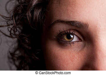 closeup of an eye of a curly haired girl with long eyelashes