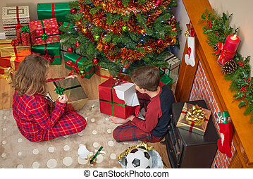 Children unwrapping Christmas presents. - Overhead photo of...