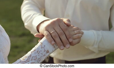 The groom gently stroking hand of the bride - Close up of...