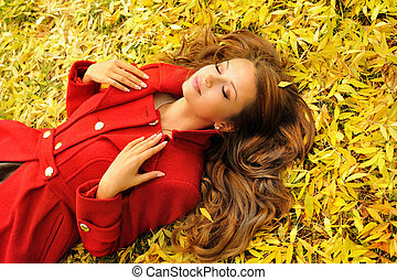 Woman in red coat lying in autumn leaves. - Attractive young...