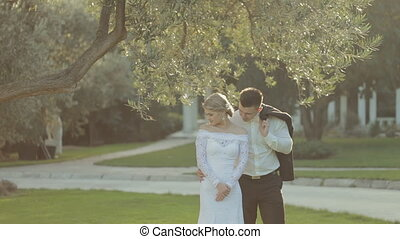 The groom comes to gorgeous bride and kisses her on the...