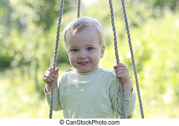 Kid on swing - Baby boy fun on a swing