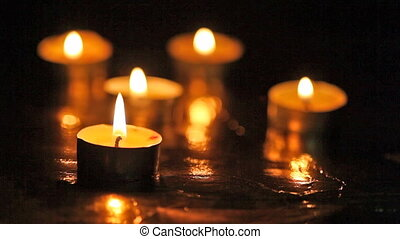 Burning small candles against a dark background with...