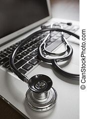 Medical Stethoscope Resting on Laptop Computer Keyboard