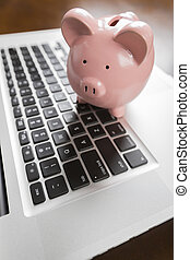 Piggy Bank Resting on Laptop Computer