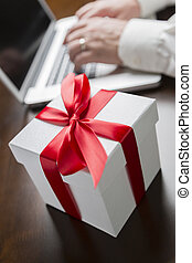White Gift Box with Red Bow Near Man using Laptop - White...