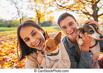 Portrait of smiling young couple with dogs outdoors in...