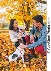 Happy young couple playing with dogs outdoors in autumn
