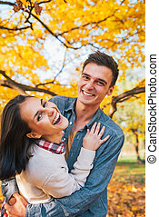 Portrait of happy young couple outdoors in park in autumn...