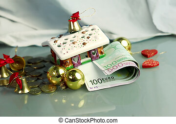 Christmas House with euro banknotes and coins around,...