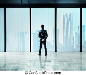 Skyscraper window - Businessman thinks about future from a...