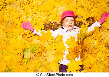 Happy smiling girl covered with autumn leaves - Happy...