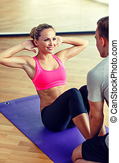 smiling woman with male trainer exercising in gym - sport,...
