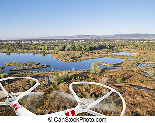 drone flying over lakes and swamp - rotating propellers of a...