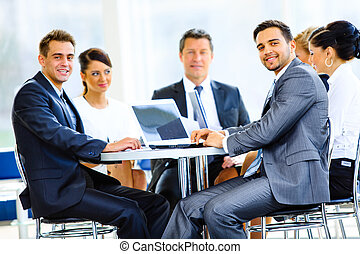 Happy businessman using laptop in business building, smiling...