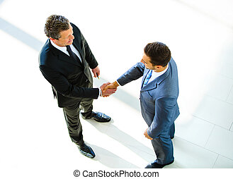 Top view of a two businessman shaking hands - Welcome to...