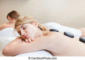 Hot stones massage - Two young pretty girls getting hot...