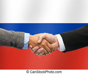 close up of handshake over russian flag - partnership,...