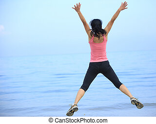 cheering woman jumping at beach