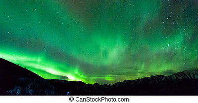 Northern Lights  - Northern lights dance over the mountains.