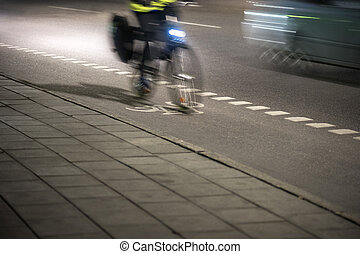 Cyclist at night - Cyclist with bicycle lamp on street at...