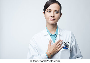 Female cardiologist touching with hand on chest - Attractive...