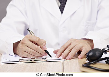 hands of doctor writing - close-up of hands of a doctor...