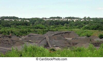 Rock quarry below homes - Rock quarry operates below a...