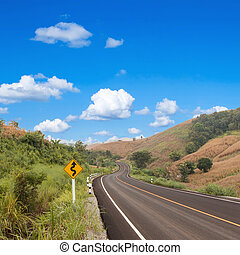 country winding road sign with blue sky