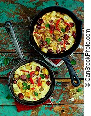 the Spanish tortilla with potatoes and sausages in small...