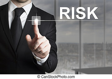 businessman pushing button risk - businessman in black suit...