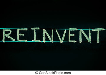 reinvent word handwritten on black chalkboard - reinvent...