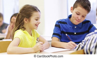 group of students talking and writing at school - education,...