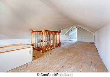Upper empty room with low vaulted ceiling, old wooden floor...