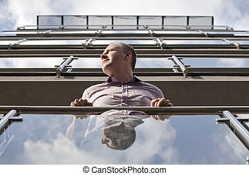 Man looking toward the sun from modern apartment - Man...