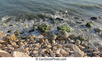 Rocky beach - Calm waves washing over smooth rocks on a...