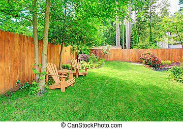Fenced backyard with green lawn and sitting area - Fenced...