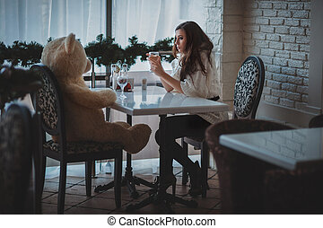 Girl with bear face to face - Girl sitting in a restaurant...
