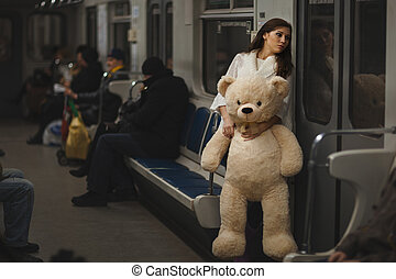 Sad girl in the subway. - Sad girl with a toy bear in the...