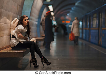 Sad girl sitting - Sad girl sitting on a bench in the subway...