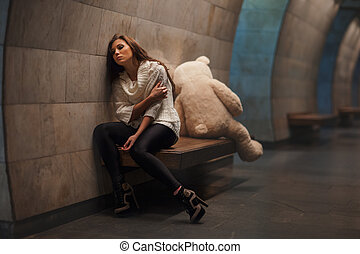 Bear and girl fight. - Girl sitting on a bench facing away...