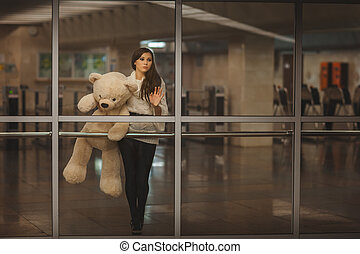 Girl waving goodbye hand - Girl with teddy bear in his hands...