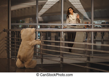Girl says goodbye with a teddy bear - Sad girl waving, she...