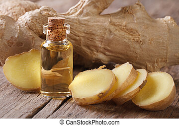 oil of ginger in a small glass bottle macro and root on the...