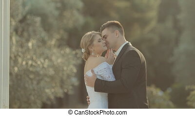 The groom gently kisses the beautiful bride in the park near...