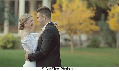 Enamoured newlyweds laughing and hugging in the park with...
