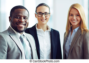 Business leader - Smiling and confident businessman with two...