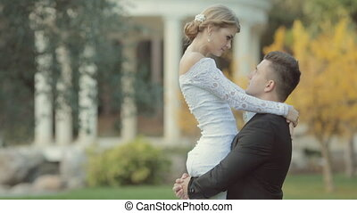 Handsome groom lifts the bride and she kisses him on the nose