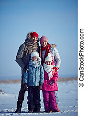 Family in winterwear - Happy parents and their kids in...